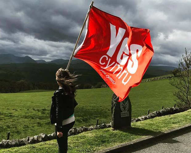 Photograph of young woman waving Yes Cymru flag